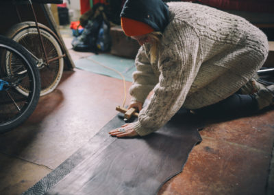 Louise Middleton kneeling on the floor cutting leather