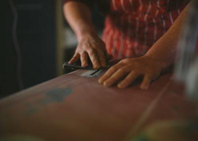 Ellies hands sanding red surfboard