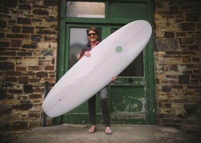 Ellie holding big white surfboard