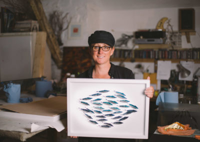 Danni Bradford holding one of her art works, which is fish gilded onto glass