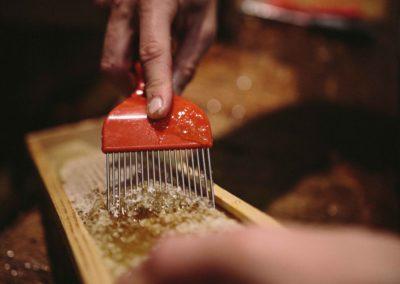 Combing honey from honey super frame