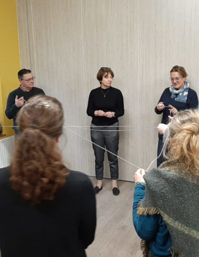 People stood in a circle holding a string, which is connecting each other