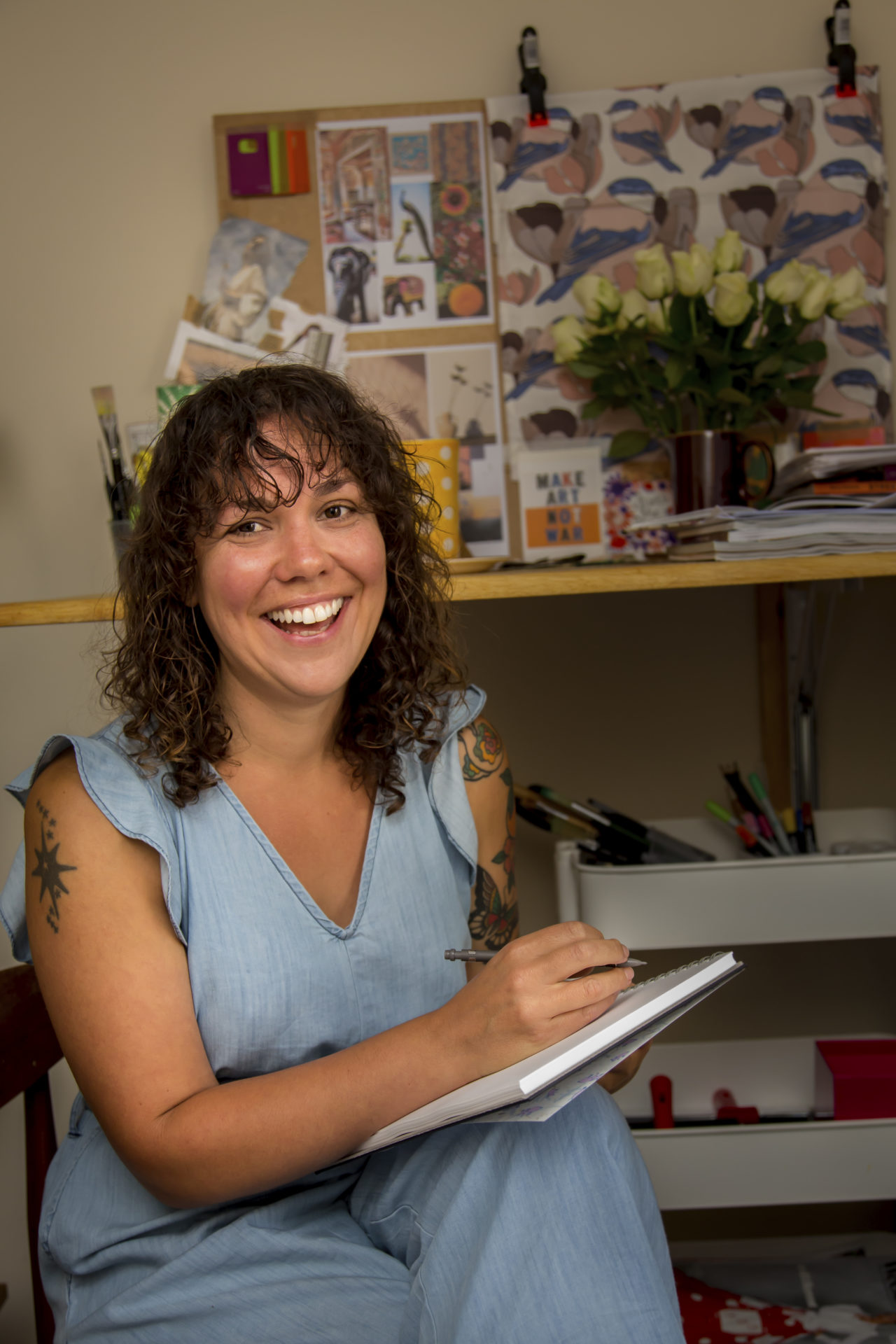 Photo of Sally smiling with sketchbook in hand