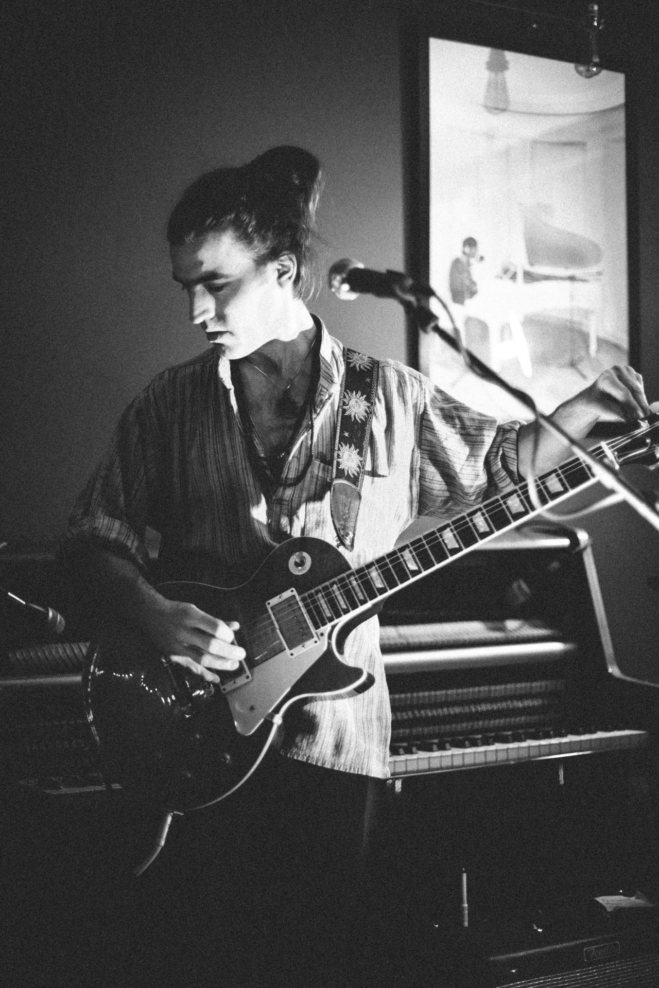 Black and White photo of David Smale tuning a guitar