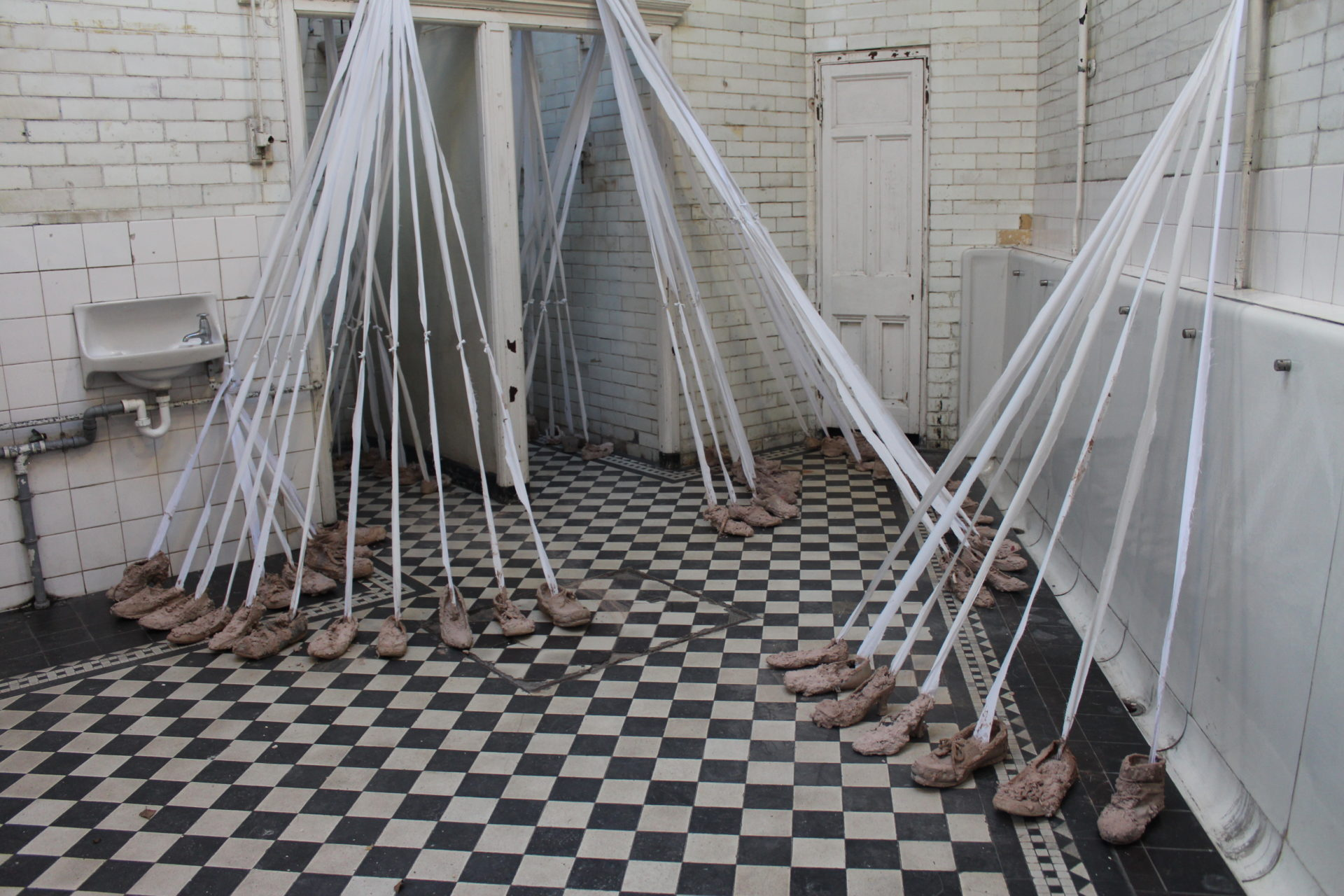 Installation Art -  shoes on a black and white tiled floor and ribbons connecting the shoes to the ceiling
