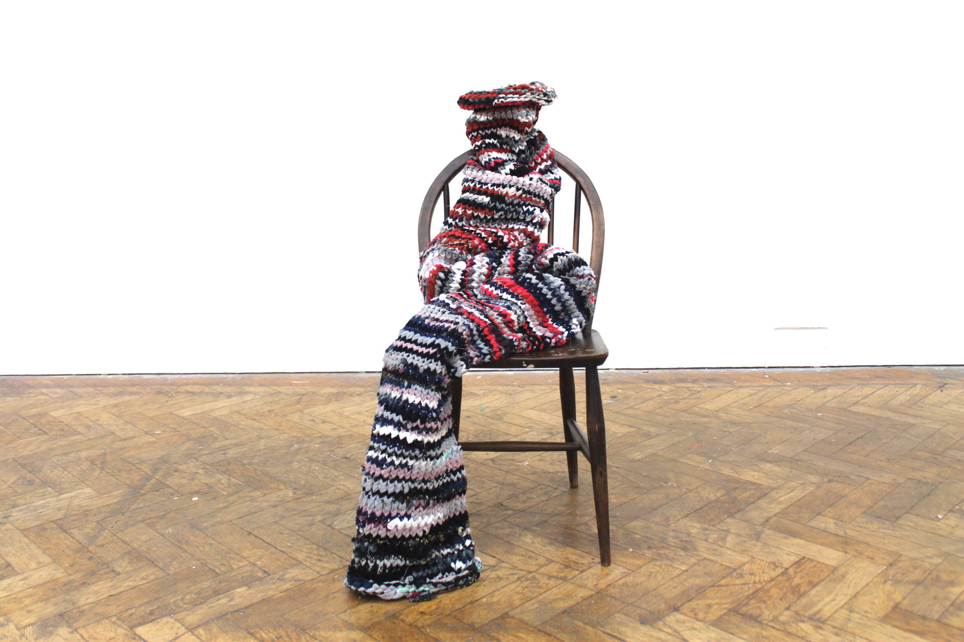 material shaped on a chair to resemble a person