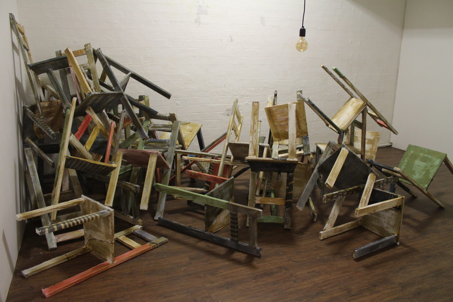 Installation of chairs piled up in a room