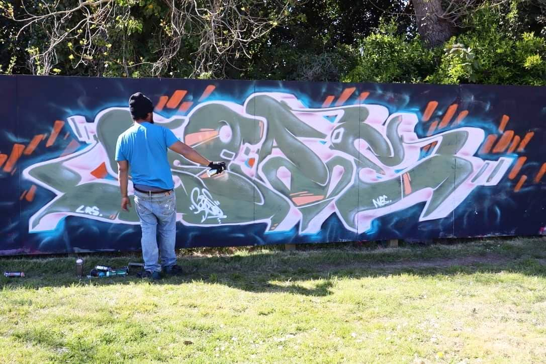 Jaz creating graffiti on a wall