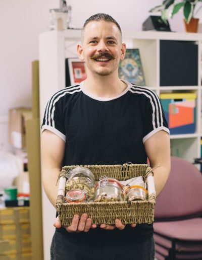 Darren Hatch smiling to camera holding a basket of mushrooms in kilner jars