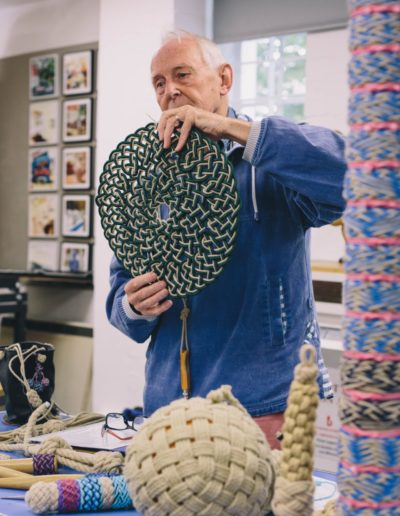 Colin Byfleet holding up a circular knotted mat
