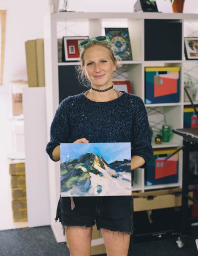 Hester Berry smiling to camera holding a painting of sand dunes