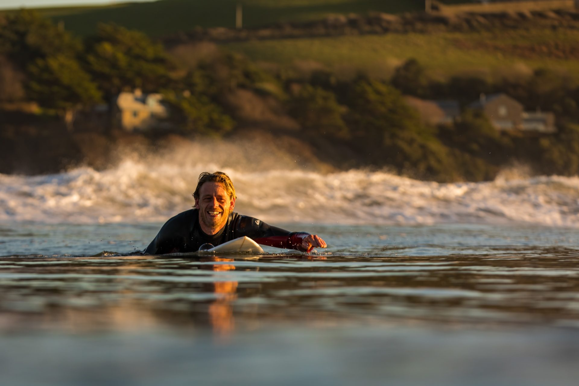 Martin Edwards on a surfboard in the sea smiling to camera