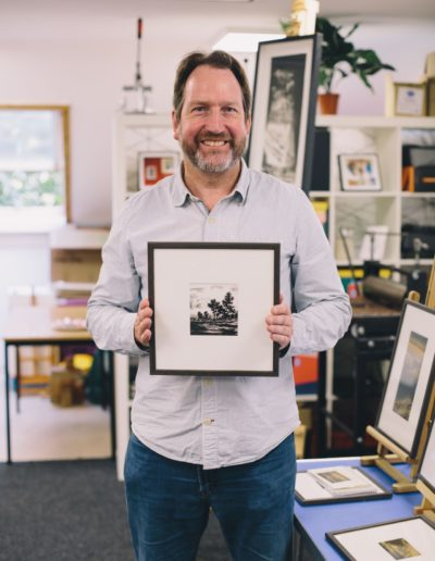 Kieron Leach holding a picture he painted on a black and white landscape