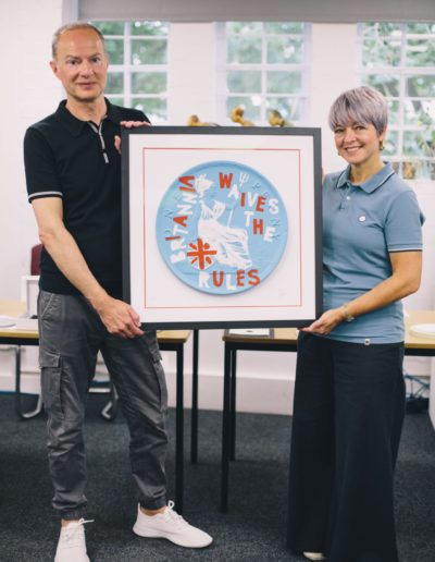 Sharon and Jason holding a print of their work together, print shows a blue decimal pennie