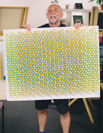 Richard Gregory holding one of his prints up which is green, blue and orange small circles