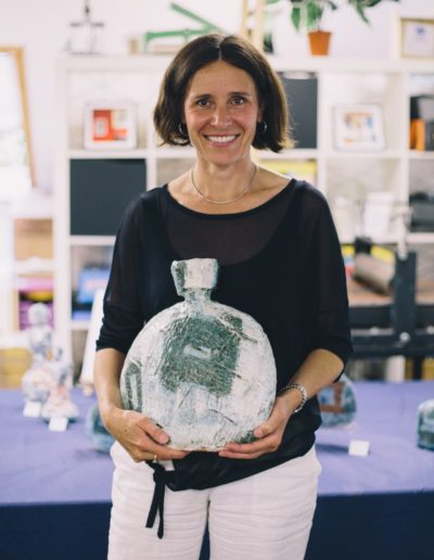 Sue Rossiter smiling to camera holding one of her large blue vessel pots